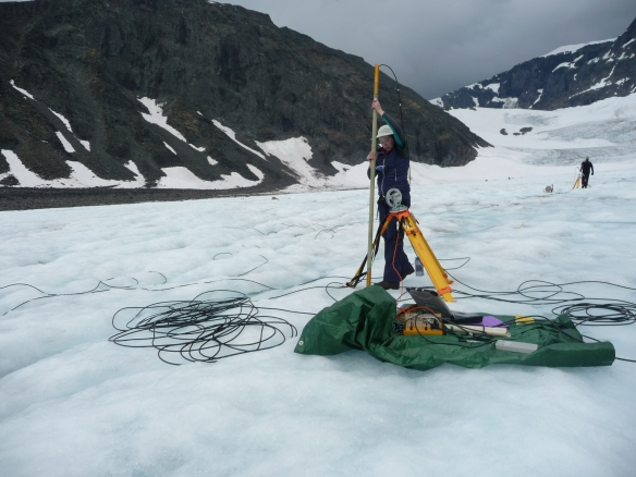 Placing the 100MHz receiver in a borehole after taking test shots along the ice surface. Optimism is always wearing a sun hat even if there is no sun!